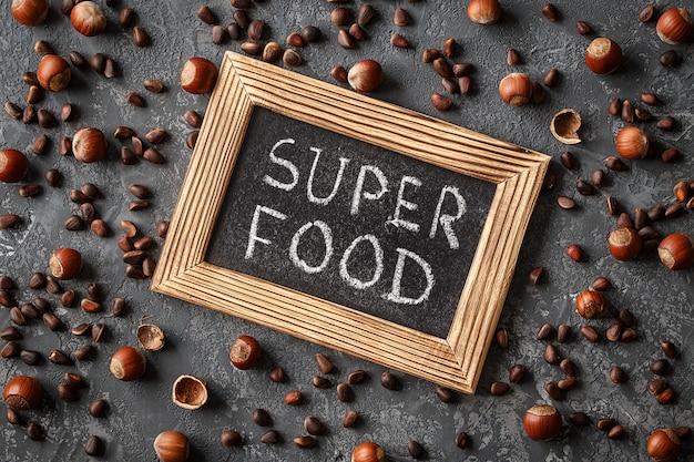 Inscriptie super food, verschillende noten op stenen tafel