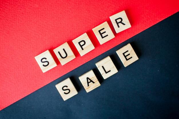 Inscriptie super verkoop van houten blokken op een zwarte en rode achtergrond
