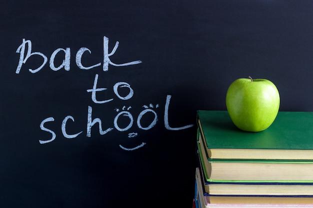 Inscriptie terug naar school apple op stapelboeken