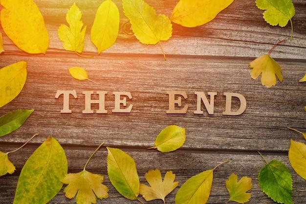 Inscriptie the end op een houten ondergrond, frame van gele bladeren
