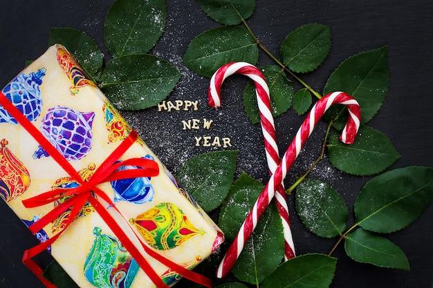 Inscriptie van het nieuwe jaar op een zwart bord met cadeau en rode snoep