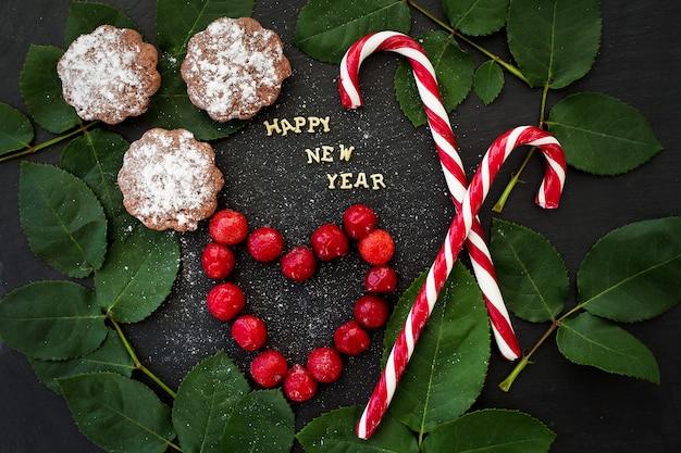 Inscriptie van het nieuwe jaar op een zwart bord met cupcakes en snoep rood