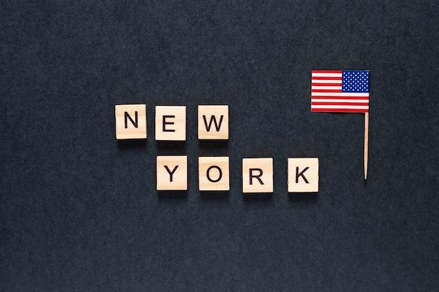 Inscriptie van new york op een zwarte achtergrond met de amerikaanse vlag.