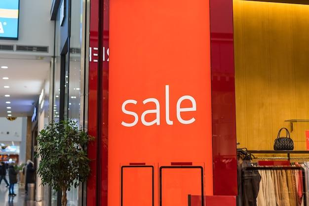 Inscriptie verkoop op de achtergrond van een rode glazen wand in de winkel
