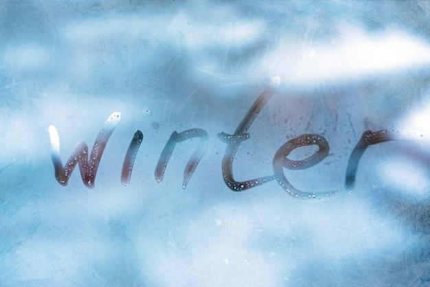 Inscriptie woord winter op het blauwe glazen venster