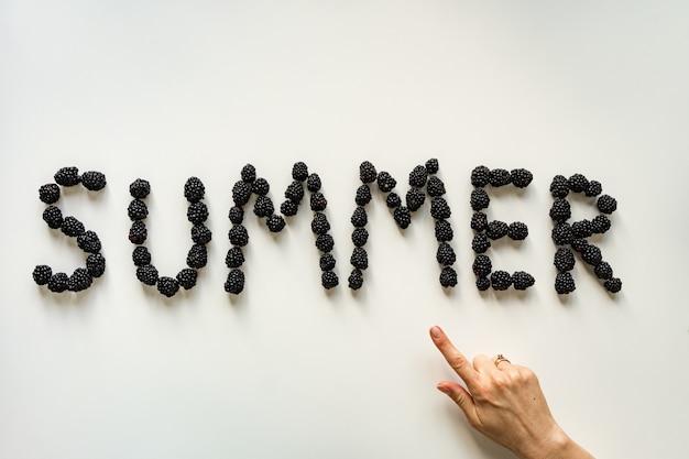 Inscriptie zomer gemaakt met bramen op wit oppervlak