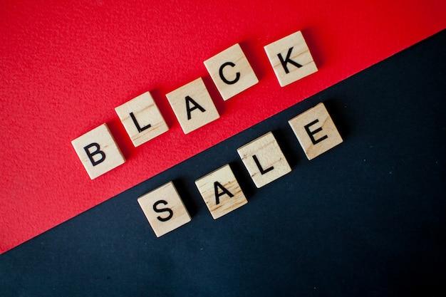 Inscriptie zwarte verkoop van houten blokken op een zwarte en rode achtergrond