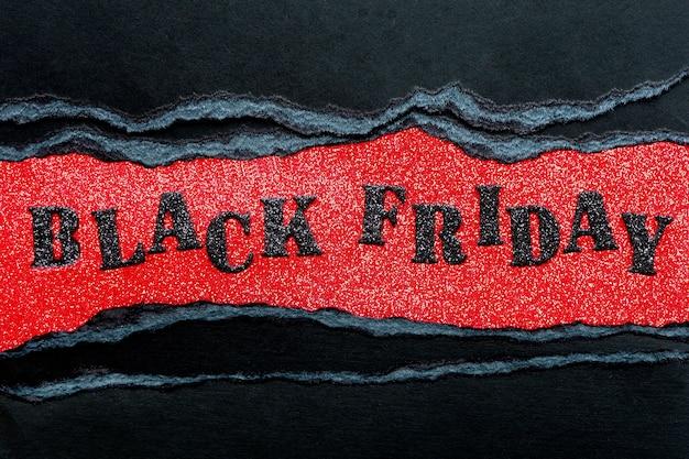 Inscriptie zwarte vrijdag in zwarte glanzende letters op een rode glanzende achtergrond en zwarte vellen karton met gescheurde randen.