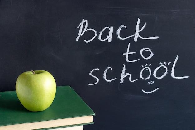 Inscriptietekst terug naar school op bord en appel op stapelboekenboeken, conceptenonderwijs