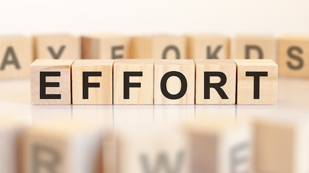Inspanning - houten letters op het bureau, witte achtergrond, bedrijfsconcept