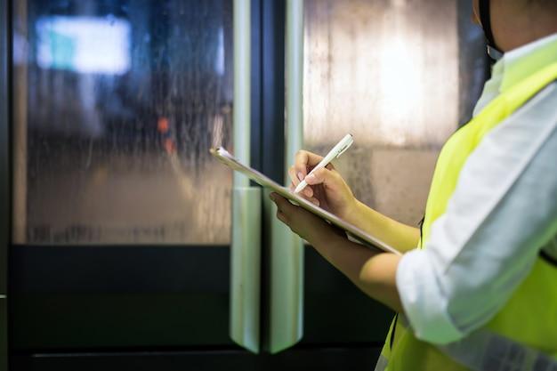 Inspecteur het schrijven nota in fabriek