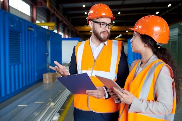 Inspecteur in gesprek met de vrouw in de fabriek