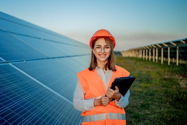 Inspecteur ingenieur vrouw met digitale tablet werken in zonnepanelen power farm