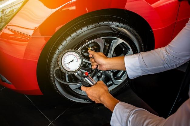 Inspectie van aziatische mensenauto meet de hoeveelheid opgeblazen rubberbanden