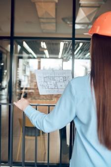 Inspiratie, baan. vrouw met lang rood haar met een bouwplan in de hand, met de rug naar de camera binnenshuis voor de glazen wand