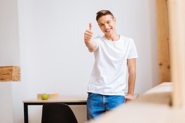 Inspiratie. goed uitziende uitbundige goedgebouwde puber die lacht en vrijetijdskleding draagt en zijn duim laat zien