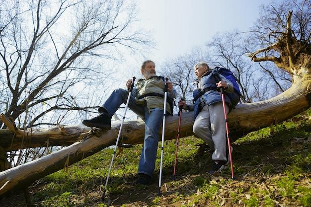 Inspiratie om te leven. leeftijd familie paar man en vrouw in toeristische outfit wandelen op groen gazon in de buurt van bomen in zonnige dag. concept van toerisme, gezonde levensstijl, ontspanning en saamhorigheid.