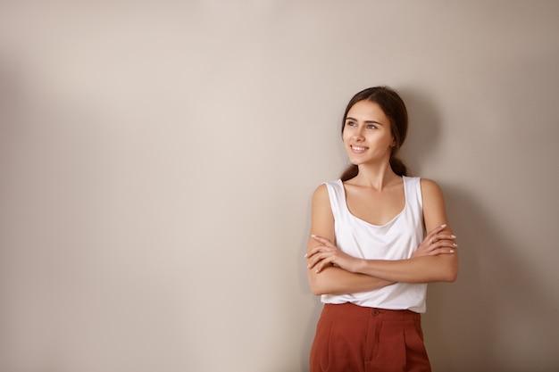 Inspiratie, vreugde en positiviteit concept. geïsoleerd beeld van zelfverzekerde gelukkige jonge vrouw met gevouwen armen opzoeken en glimlachend in grote lijnen poseren in nieuw leeg appartement, na te denken over toekomstig interieur