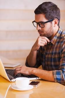 Inspireren met kopje verse koffie. zelfverzekerde jonge man die op laptop werkt terwijl hij in de coffeeshop zit
