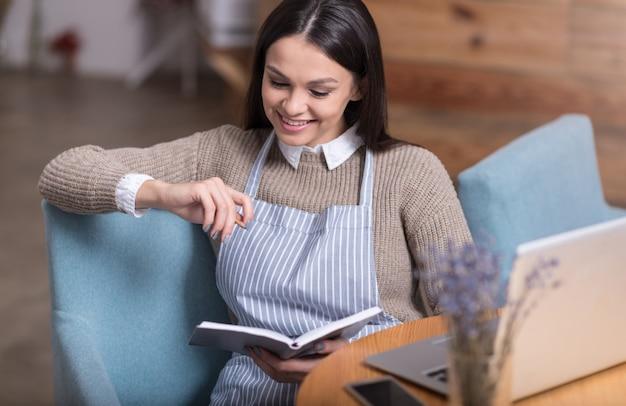 Inspirerend werk. emotionele mooie jonge vrouw lachen en notities maken zittend bij de tafel.