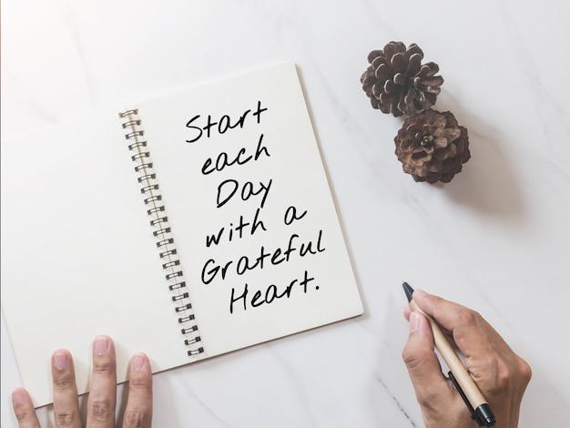 Inspirerende, motiverende citaat op notebook met dennenappel en handen schrijven