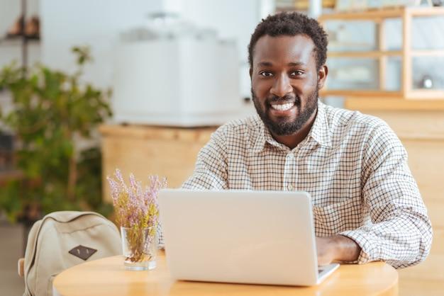 Inspirerende sfeer. knappe vrolijke man zit aan de tafel in een café en werkt op de laptop terwijl hij lacht naar de camera