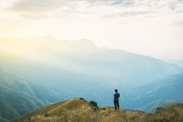 Instagram-filter jonge man asia-toerist bij berg waakt over de mistige en mistige ochtend zonsopgang