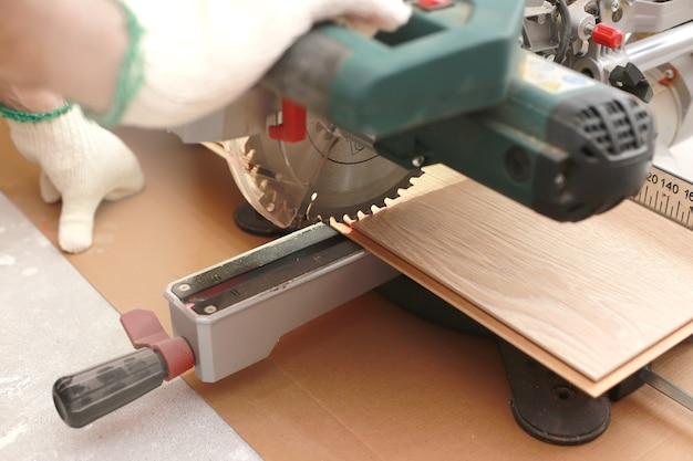 Installatie laminaat of parket in de kamer, werknemer snijdt een laminaat van een bepaalde lengte met een elektrische zaag. zelfreparatie van de vloer in het huis.