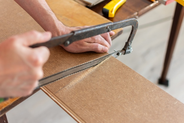 Installatie laminaat of parket in de kamer, werknemer zaagt een laminaat van een bepaalde lengte met een zaag