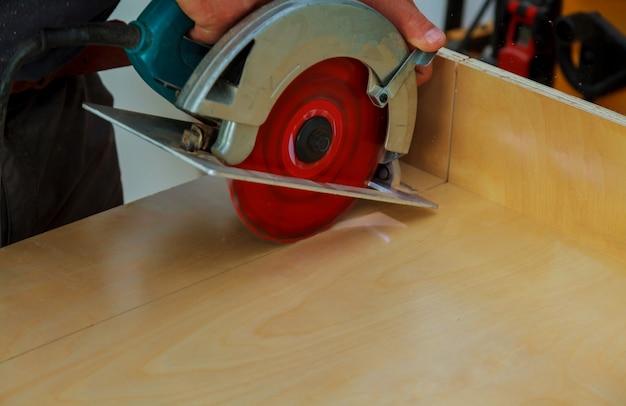 Installatie van de keuken. werknemer met behulp van circulaire elektro zaag snijden keukenkast