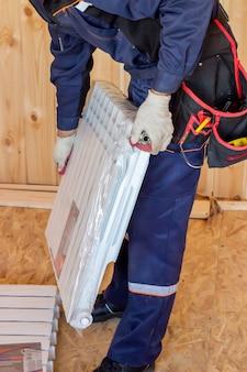 Installatie van de verwarmingsradiator. bouw van huizen en appartementen. bouwer.