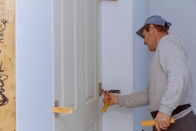 Installatie van deuren op arbeider die luchtnagelgeweer van nieuw huis met behulp van