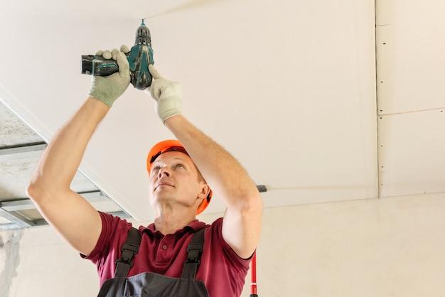 Installatie van gipsplaat met en een schroevendraaier om gipsplaat aan het plafond te bevestigen