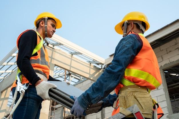 Installatie van keramische dakpannen door dakdekker, concept van woongebouw in aanbouw.