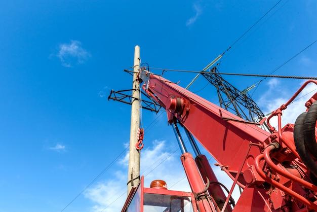 Installatie van kolom voor elektriciteitslijn met hoog voltage tegen de achtergrond van blauwe hemel op een zonnige de zomerdag