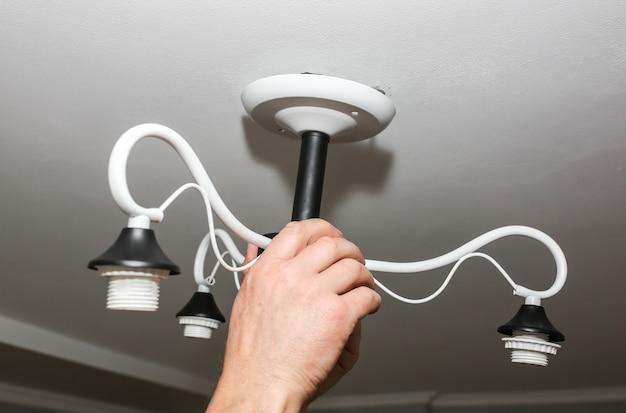 Installatie van lampen. man bedrijf bouw. restauratie binnenshuis. onderhoudswerkzaamheden.