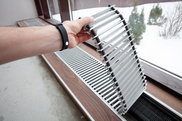 Installatie van verwarmingsconvector ingebouwd in de betonnen vloer.
