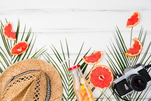 Installatiebladeren dichtbij citrusvruchten en hoed met camera