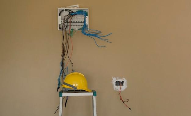 Installeer de bedrading van de stroomonderbrekerkaart elektrisch op de muurachtergrond en veiligheidshelm