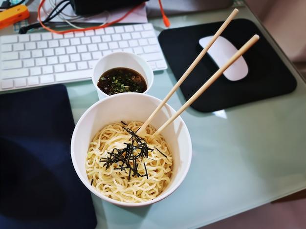 Instant cup-noedels op rommelige tafel tijdens thuiswerken in quarantaineperioden