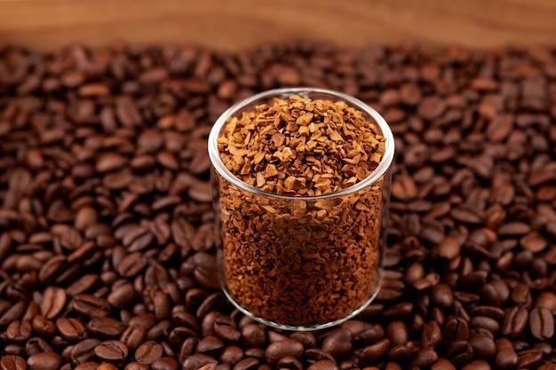 Instant gevriesdroogde of gegranuleerde koffie in glas op achtergrond van gebrande koffiebonen