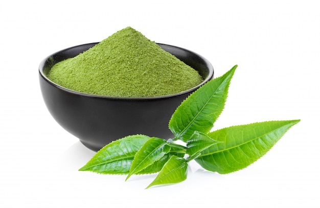 Instant matcha groene thee in zwarte kom en blad op wit