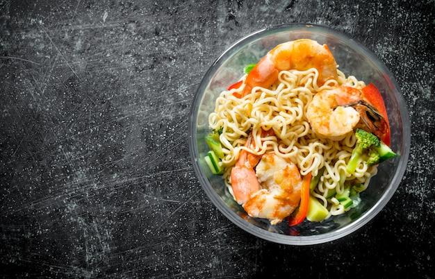 Instant noedels in een glazen kom met garnalen en groenten op zwarte rustieke tafel