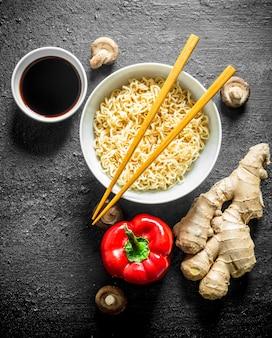 Instant noedels in kom met paprika, gember en sojasaus op zwarte rustieke tafel