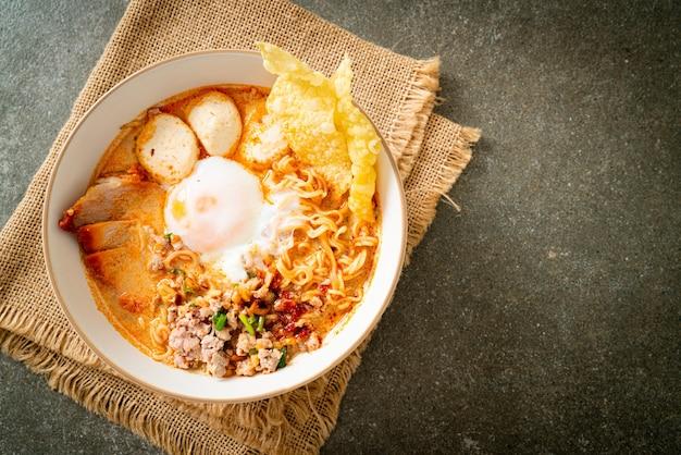 Instant noedels met varkensvlees en gehaktballen in pittige soep of tom yum noodles in aziatische stijl