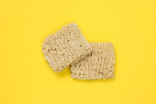 Instant noedels, ramen, gedroogde noedelblokken op een gele muur. ongezonde voeding concept. ongekookte pasta. bovenaanzicht. traditionele japanse keuken.