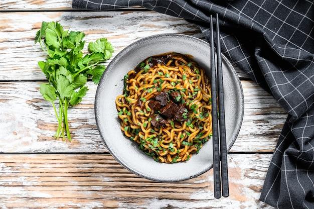 Instant ramen noodles met koriander en tofu in een gietijzeren pot. vegetarisch gerecht. witte houten achtergrond. bovenaanzicht