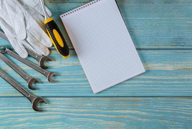 Instellen van gereedschappen voor automonteur, werkhandschoenen in steeksleutel auto spiraal notitieblok