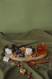 Instellen voor het drinken van thee. diverse snoepjes, noten en honing voor thee op een houten snijplank. walnoten, amandelen, hazelnoten, dadels, rahatlukum, honing, gedroogd fruit. gezonde snoepjes, natuurlijke snoepjes.