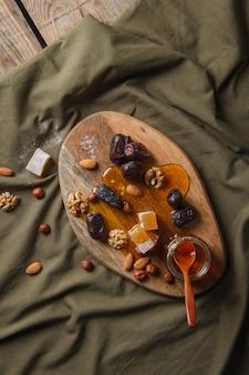 Instellen voor het drinken van thee. diverse snoepjes, noten en honing voor thee op een houten snijplank.